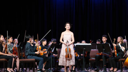 Violinist with orchestra behind her on stage.