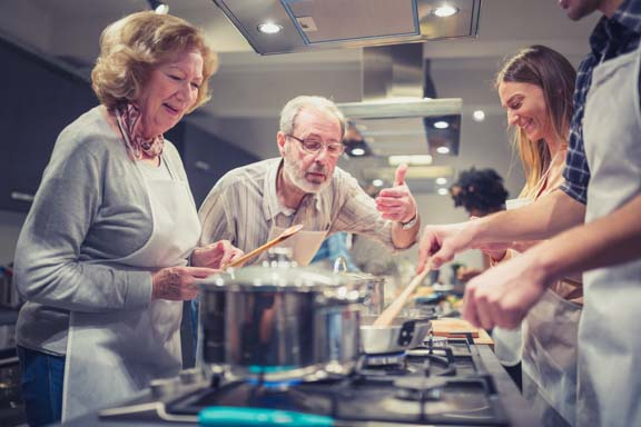 Participants of a cooking class in a modern kitchen cooking together and having fun.