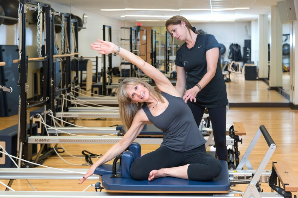Women getting a private training session with a pilates machine.
