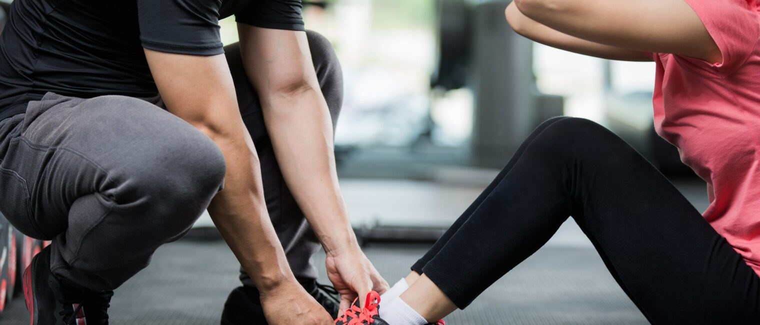 Trainer holding a woman by the shoes as she does sit ups.