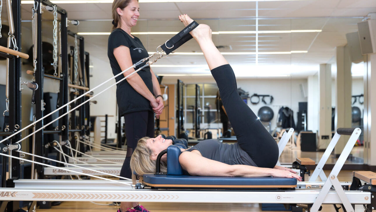Woman doing pilates on the reformer machine.