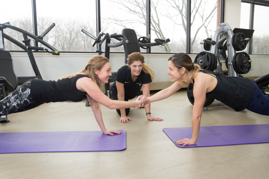 Two women giving each other high fives as they hold high planks.