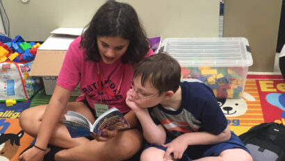 Teen girl reading to a young boy.