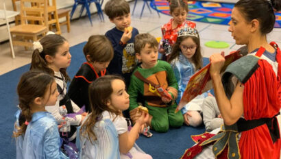 Kids dressed up in costumes listening to the teacher read a book.