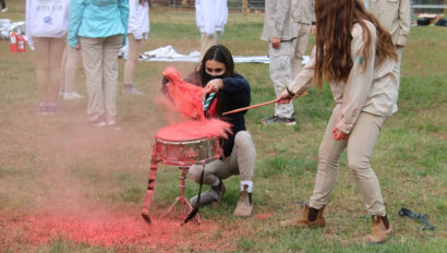 Girl banging a drum while another girl pours red dust on the drum.
