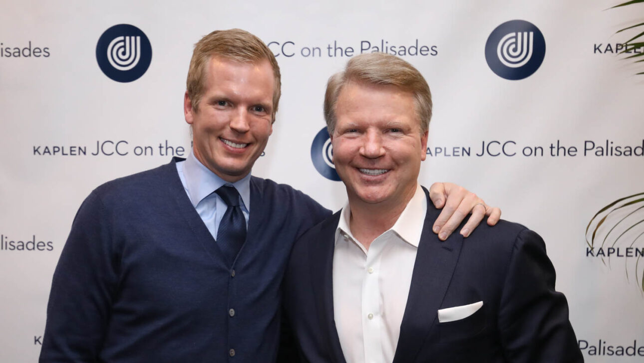 Two person photo with JCC logo backdrop.