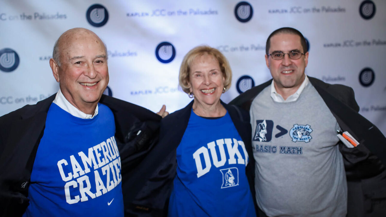 Three people photo with JCC logo backdrop.