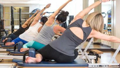 Women doing poses on pilates reformer machines.