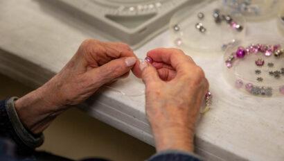 Senior beading a bracelet.