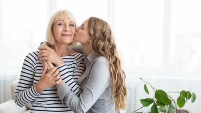 Daughter kissing senior mother on the cheek.