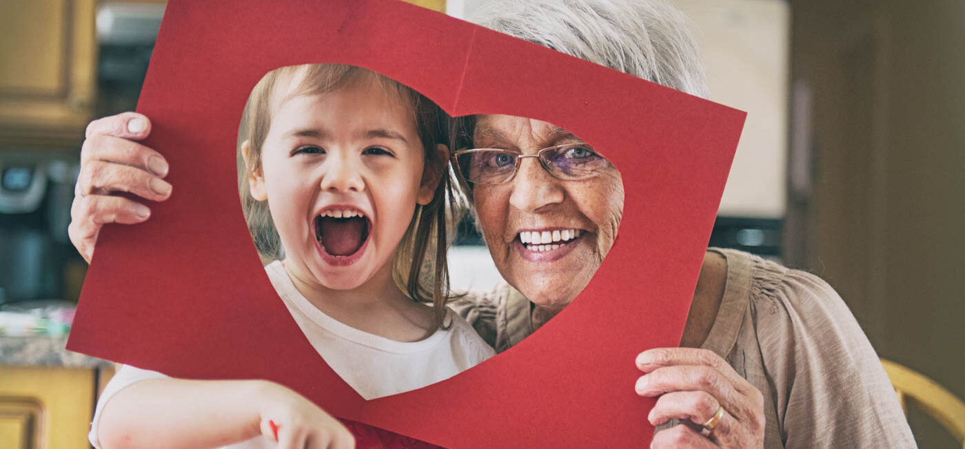 Senior woman with her grandchild and a paper heart cut out.