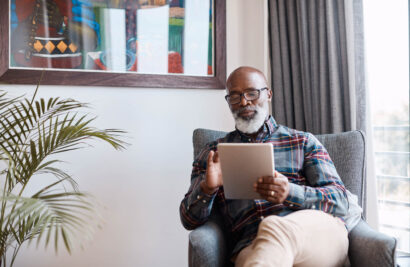 Senior man reading on an ipad.