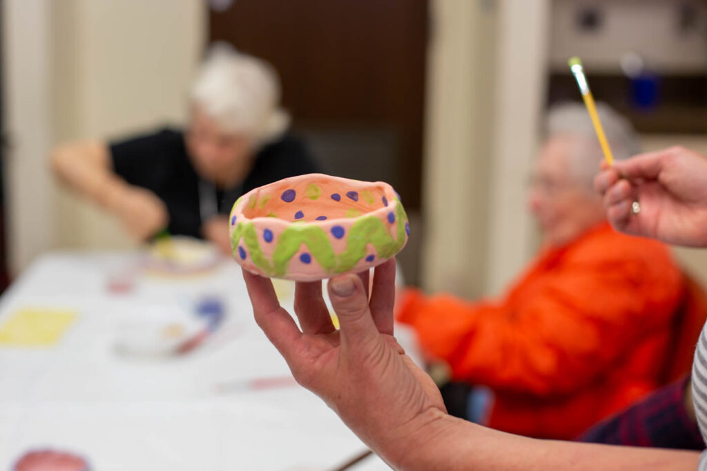 Seniors painting pottery.