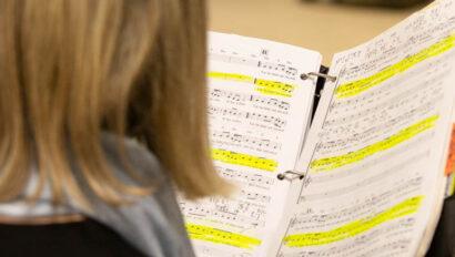 Woman holding sheet music.