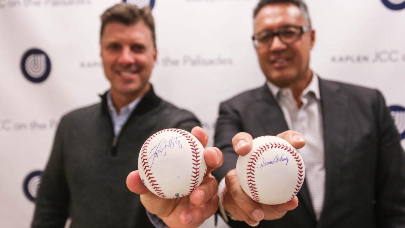Two guys holding up signed baseballs.