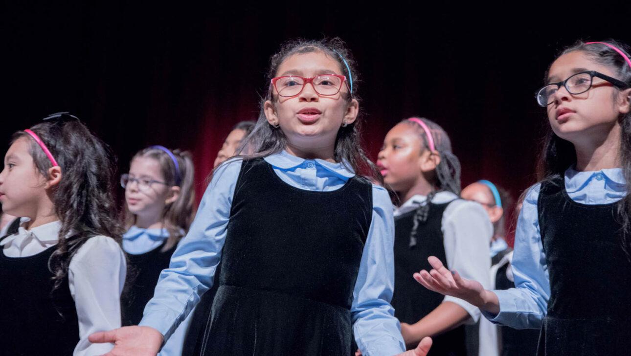 Girls singing on stage.