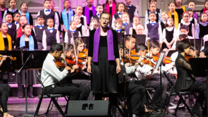 Choir and orchestra performing together on stage.