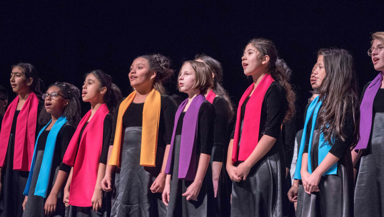 Girls in colored scarves singing on stage.