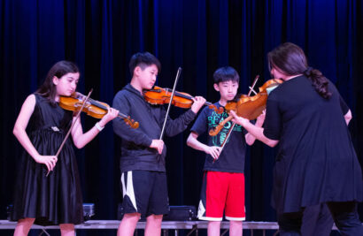 Three boys playing the violin with a teacher.