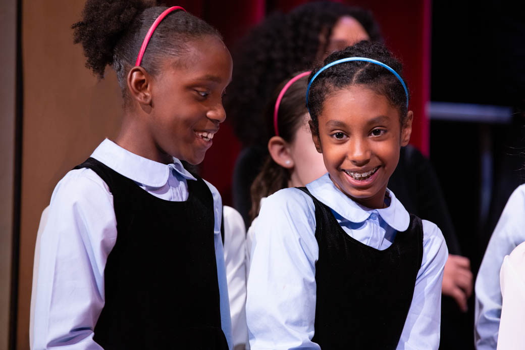 Two young girls smiling at each other on stage.