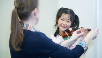 Teacher showing young girl how to hold a violin.