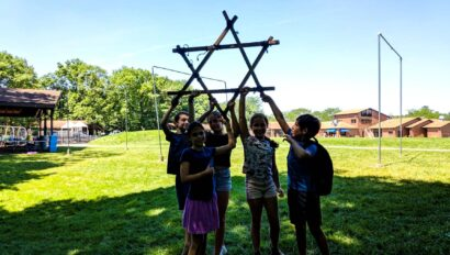 Campers holding a star of david made of wood.