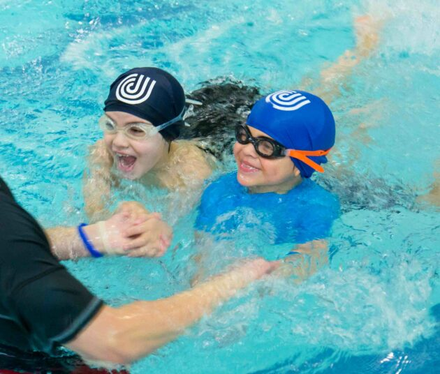 Kids in a pool swimming.