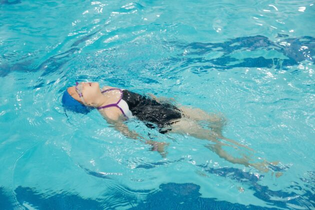 Child practicing floating in a pool.