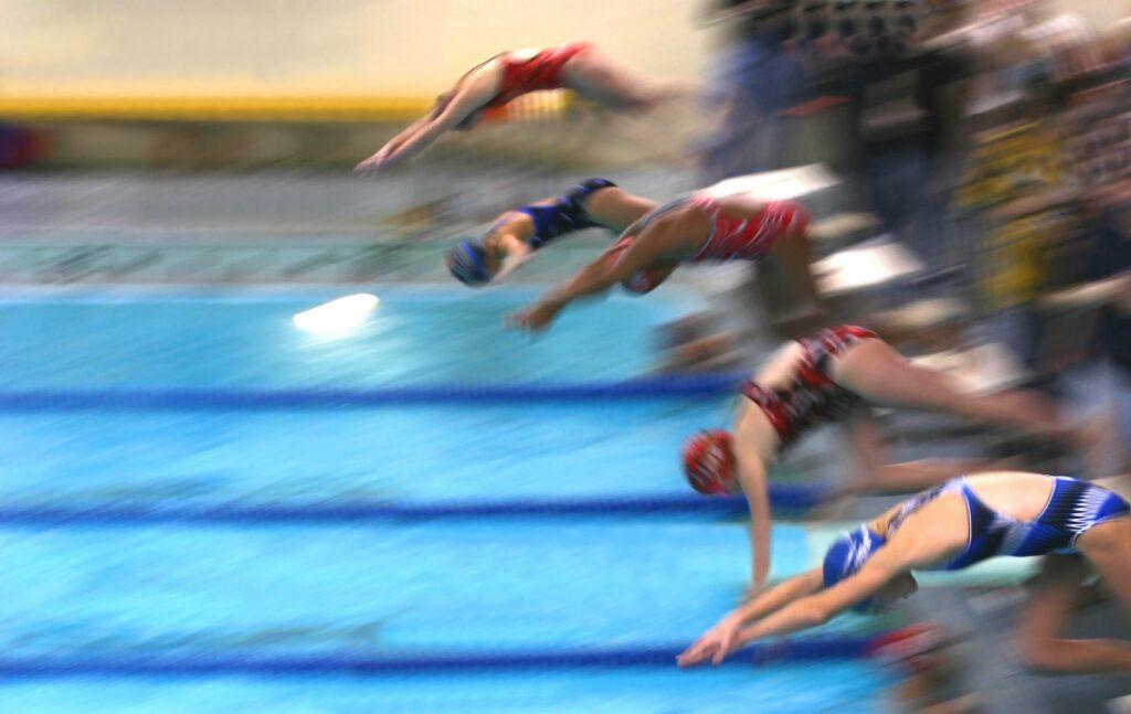 Action shot of swim racers starting off the blocks.