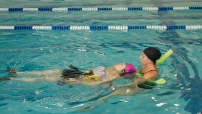 Swim instructor helping a woman swim in the pool.