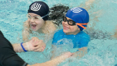 Two children taking swimming lessons.