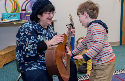 Teacher holding guitar while toddler touches it.