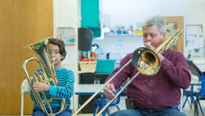 Teacher playing a brass instrument along side young boy.