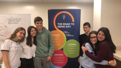 Teens in front of a Demo Day poster.