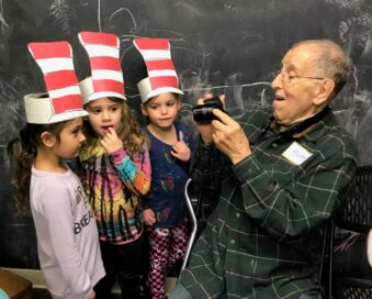 A teacher takes a close-up picture of three young students wearing their hat art projects.
