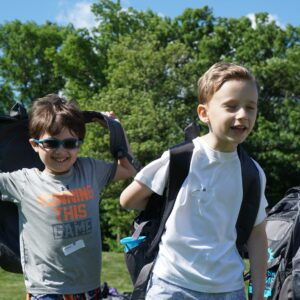 Three boys wearing backpacks run in a field. They're smiling.