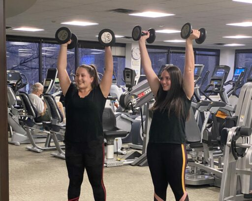 Two women lift kettlebells. They are dressed in black shirts and black tights with white tennis shoes.