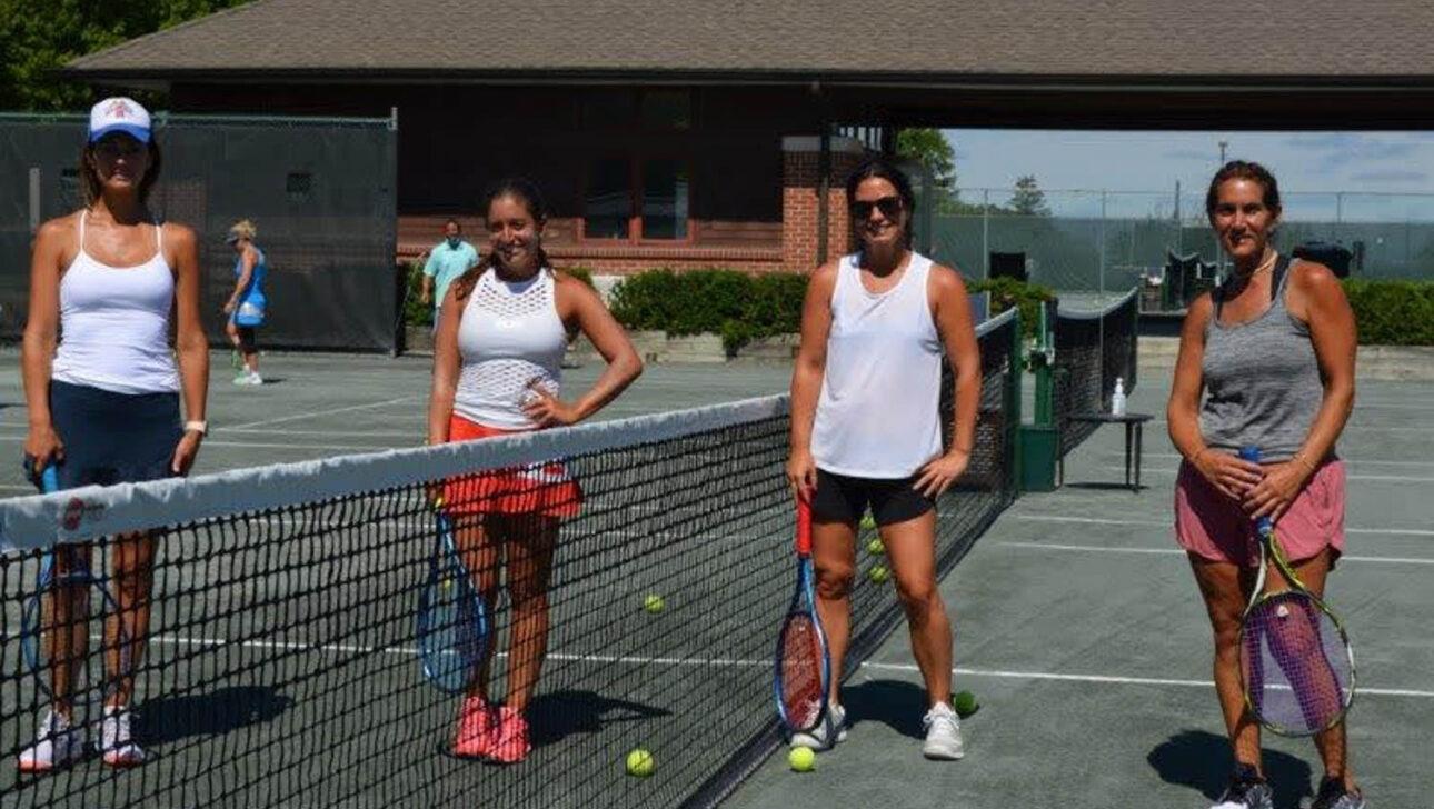 Four ladies on a tennis court.