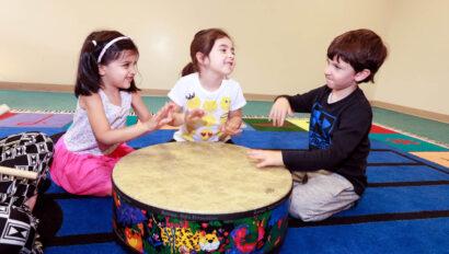Three children playing a drum.