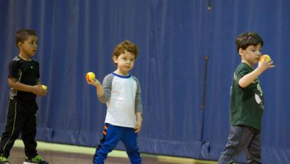 Toddler doing tennis drills inside.