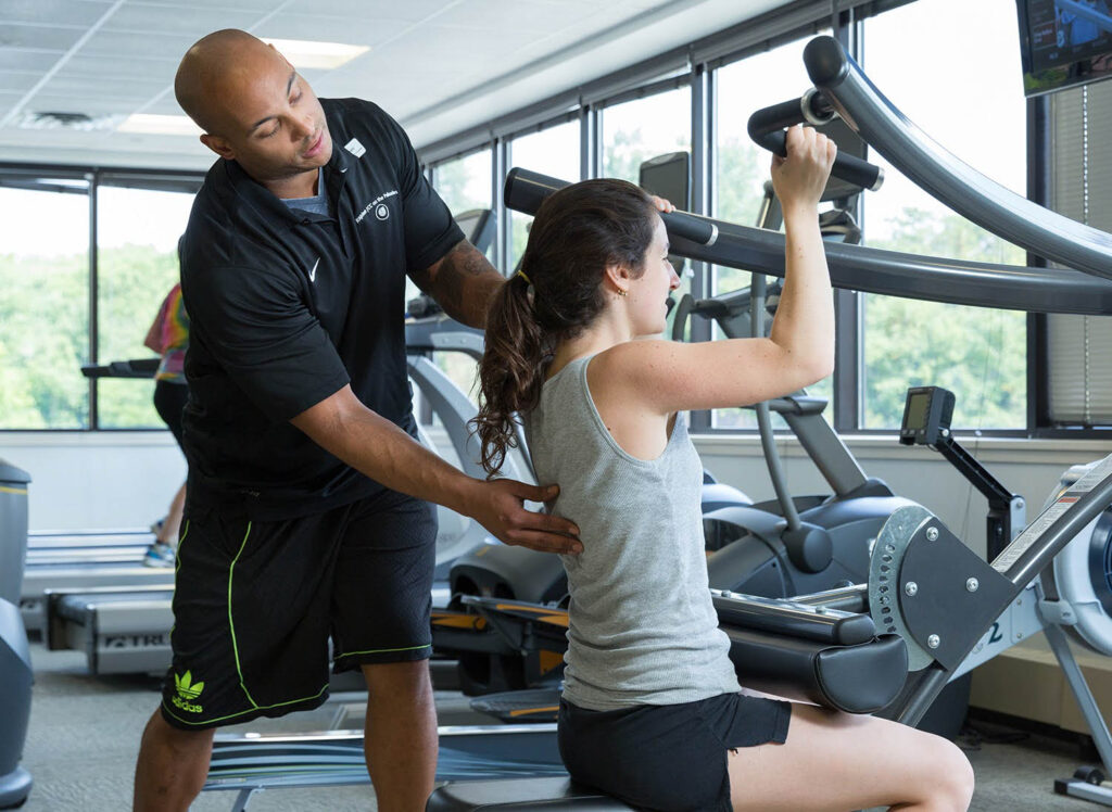 Personal trainer training a woman in the gym.