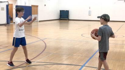 Two boys playing basketball.