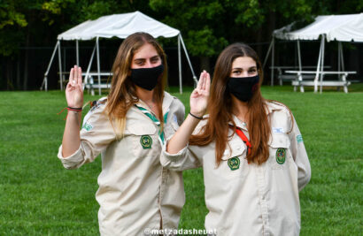 Two girls in scouts uniforms holding up three fingers.