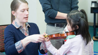 Two teachers teaching a young girl the violin.