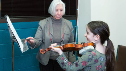 Teacher instructing a girl in the violin.
