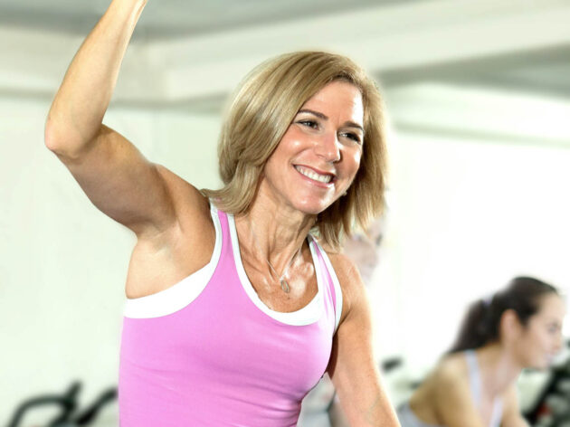 Woman excited in a cycling class.