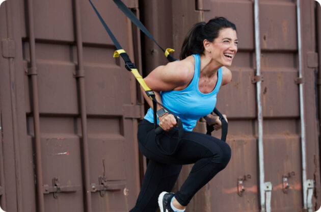 Woman doing exercise with TRX straps.