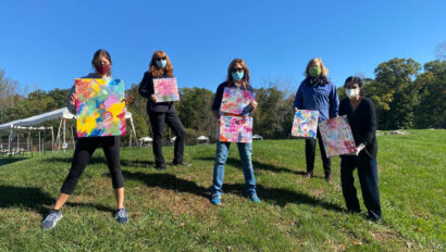 Group of women holding up their paintings outside.
