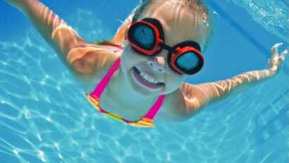 Young girl with goggles under water.