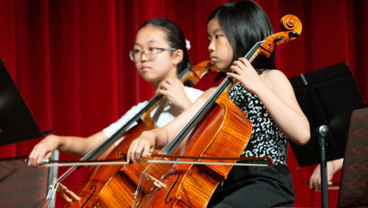 Girls playing the cello on stage.